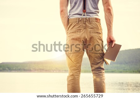 Young Man standing with book outdoor with scandinavian lake on background Education and Lifestyle Travel concept - stock photo