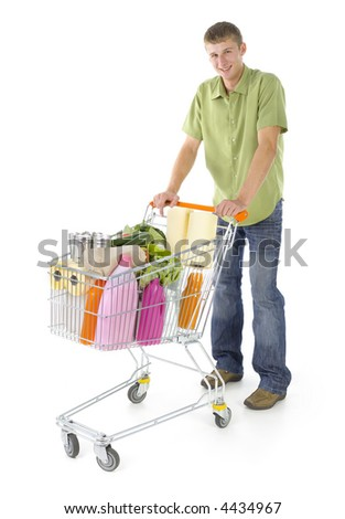 Young man standing with full of things trolley. Smiling and looking at camera. Isolated on white in studio. Front view, whole body