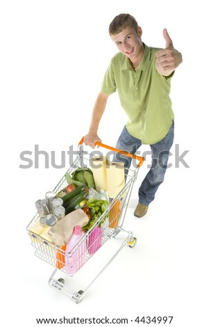 Young man standing with full of things trolley. Smiling and looking at camera. Isolated on white in studio. Whole body, thumb up - stock photo