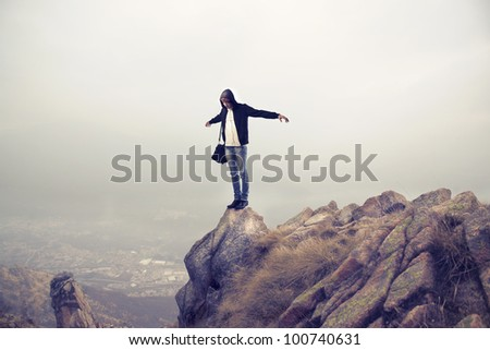 Young man standing with open arms on a mountain peak - stock photo