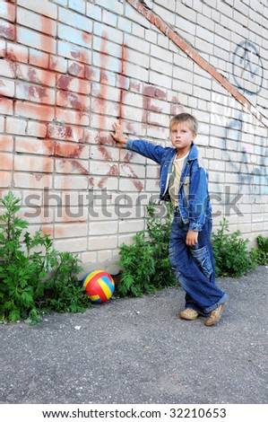 young man stands against graffiti