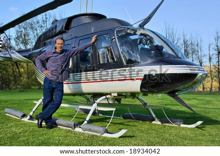 Young man stands next to small private helicopter on grass in estate. Shot  near Cape Town, Western Cape, South Africa. - stock photo