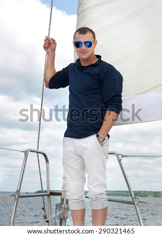young man stands on deck of a yacht under a sail in sunglasses