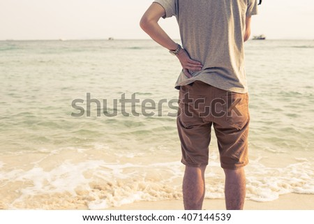 Young man stands on the beach