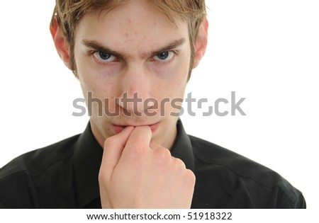 Young man stares into space concentrating on thinking and planing about greed, jealousy, and lust, - stock photo