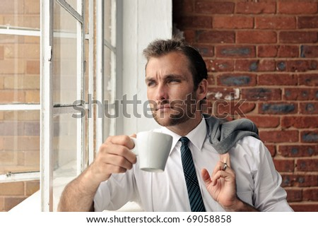 young man stares out the window while holding a coffee cup - stock photo