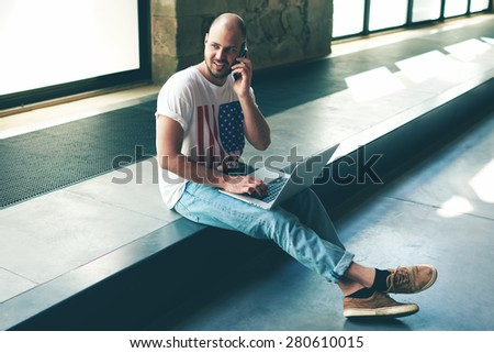 Young man starting business sitting on the floor of his empty office building with on laptop computer while he talk on smart phone about the project, architect discussing about interior design studio  - stock photo
