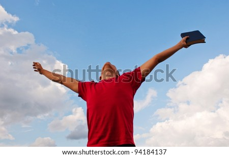 Young man staying with raised hands against blue sky - stock photo