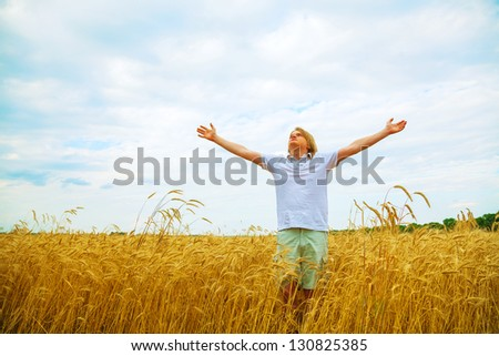 Young man staying with raised hands at sunset time