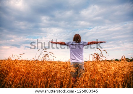 Young man staying with stretched out hands at sunset time - stock photo