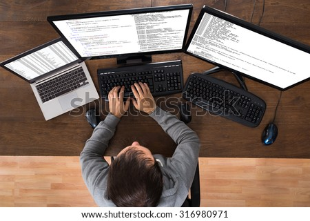 Young Man Stealing Data From Computers And Laptop At Desk - stock photo