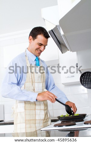 young man stir fry vegetable in kitchen
