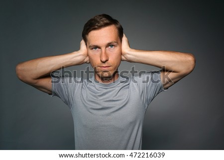 Young man stopped his ears with hands.