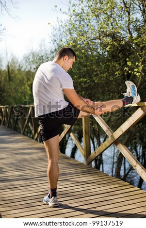 Young man stretching at the park - stock photo