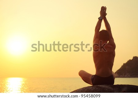 Young man stretching on a rock at sunset light