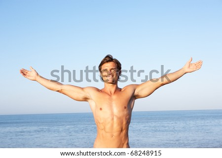 Young man stretching on beach - stock photo