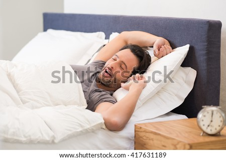 Young man stretching while waking up in the morning. Man yawning while waking up. Lazy young man in sleep. Portrait of latin man yawns and stretches in bed. - stock photo