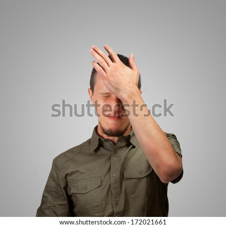 Young man strikes his forehead, concept of failure - stock photo