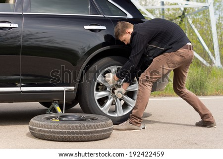 Young man struggling to change his car tyre as he battles with a wheel spanner to loosen the nuts on the hub standing putting his weight behind the effort - stock photo