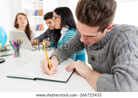 Young man student sitting and writing in the foreground. A happy group of his friends is behind him and looking at laptop.  - stock photo