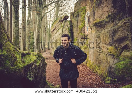 Young Man,Student smiling hiking in forest.Man hiker smiling happy portrait on foggy day during a trekking trip. Back of a young man outdoors in nature on a hiker path in forest. - stock photo