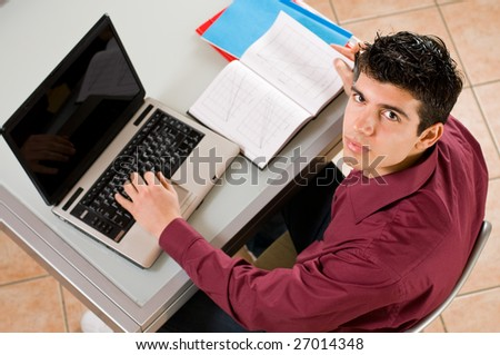 Young man studying and working on his laptop with note pad.