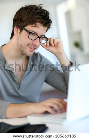 Young man studying from home - stock photo