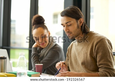Young man studying hard with woman sitting by. University students preparing for final exams.