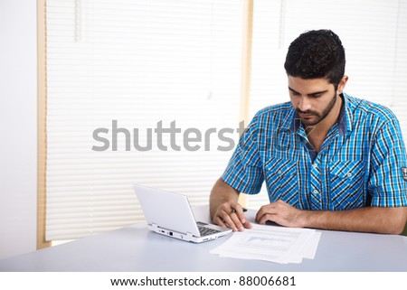 Young man studying or working with a computer and documents. - stock photo