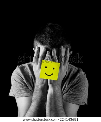 young man suffering depression and stress sitting alone in pain and grief feeling desperate with yellow note happy smiley face stuck on his hands isolated on black background - stock photo