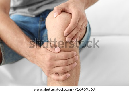 Young man suffering from leg pain at home