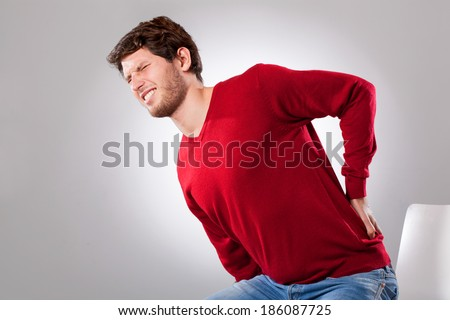 Young man suffering from strong backache, horizontal - stock photo