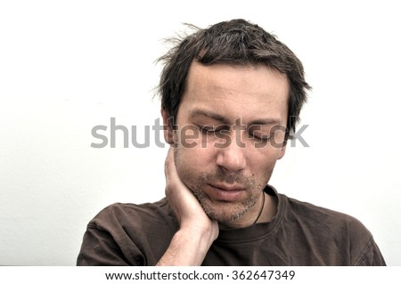 Young man suffering from toothache, teeth pain, swollen face - stock photo