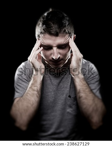 young man suffering migraine and headache in intense pain feeling desperate and sick with hands on tempo in stress isolated on black studio background - stock photo