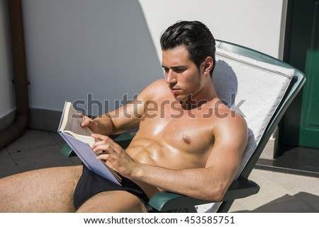 Young Man Sunbathing on Lounge Chair Reading Book