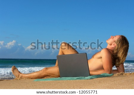 Young man sunbathing with notebook on beach. Shot in Sodwana Bay nature reserve, KwaZulu-Natal province, Southern Mozambique area, South Africa.