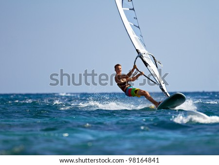 Young man surfing the wind on a bright summer day - stock photo