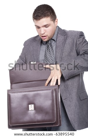 young man surprised after looking his briefcase - stock photo