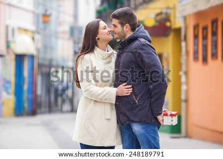 Young man surprising his girlfriend for Valentine's day or birthday - stock photo