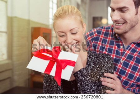 Young man surprising his sweetheart with a gift tied in a large red bow for Valentines Day as he approaches her from behind in an intimate embrace - stock photo