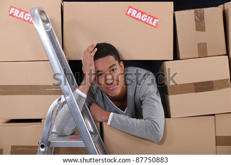 young man surrounded by boxes moving into a new apartment - stock photo