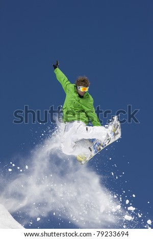 Young man suspended in mid-air making snowboard  jump.