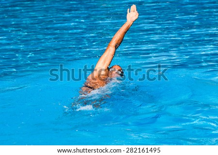 young man swim backstroke style in outdoor swimming pool, sunny summer day - stock photo