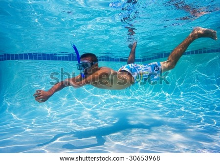 Young Man Swimming in Pool Underwater - stock photo