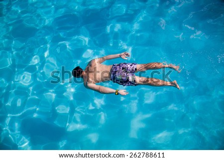 Young  man swimming  in the blue water