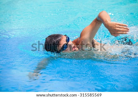 Young man swimming the front crawl/freestyle in a pool - stock photo