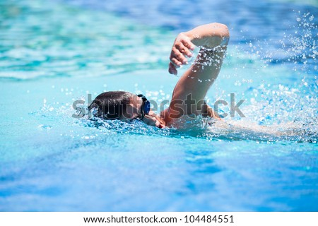 Young man swimming the front crawl in a pool - stock photo