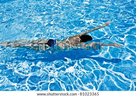 Young man swimming under blue  water in swimming pool