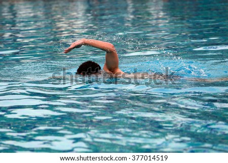 Young man swimmingl in a pool