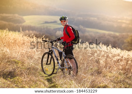Young man takes a break in a field while mountain biking - stock photo